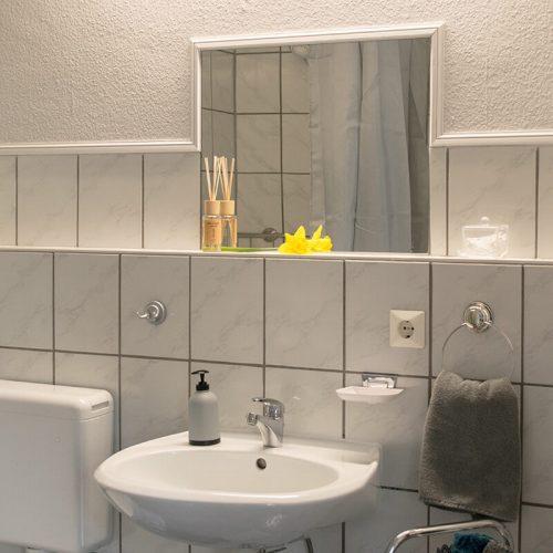 Badezimmer-mit-Spiegel-und-Waschbecken