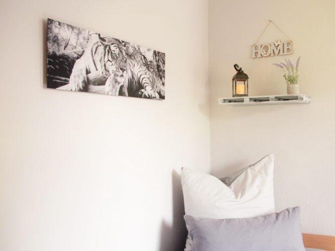 Zimmervermietung-Bernburg-Blick-aufs-Bett-mit-Bild-und-Kerze